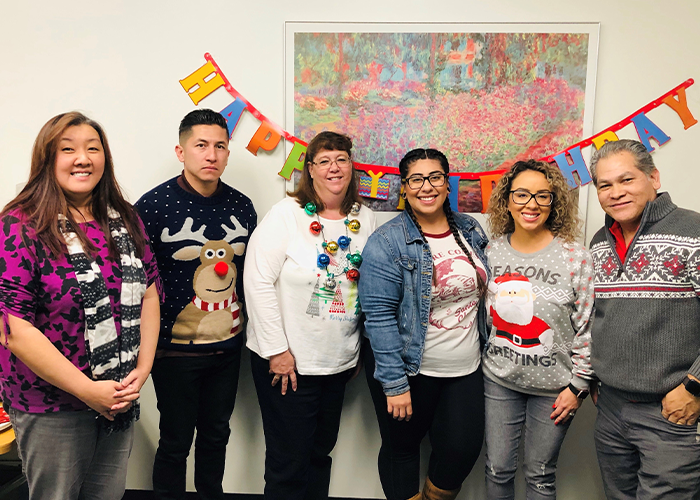 Employees together wearing holiday sweaters.